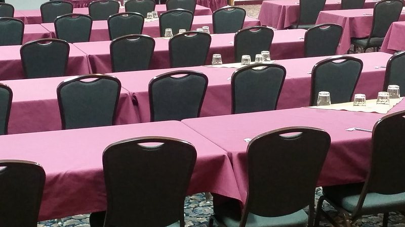 Rows of tables and chairs in hotel conference room