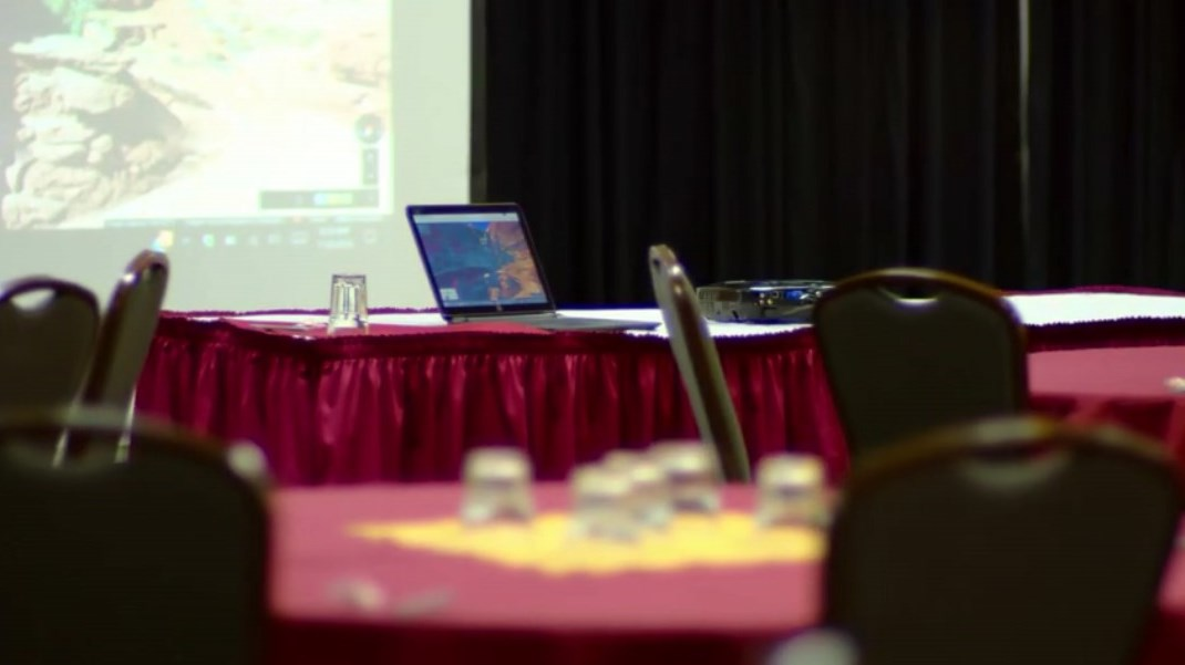 A laptop connects to a projector in a hotel conference room